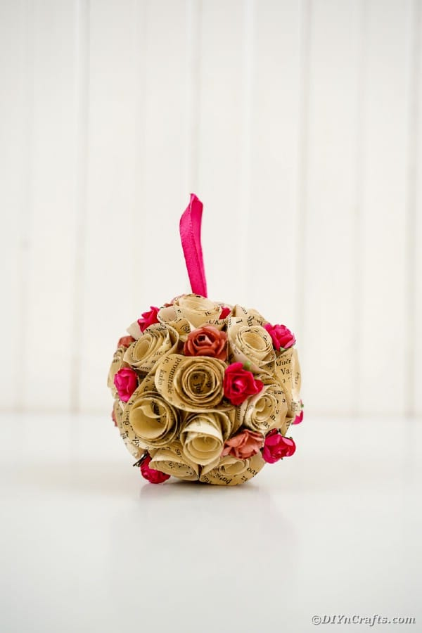 Paper rose ball ornament in front of whtie wooden wall