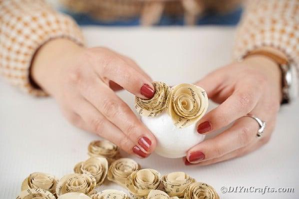 Gluing paper roses to styrofoam ball