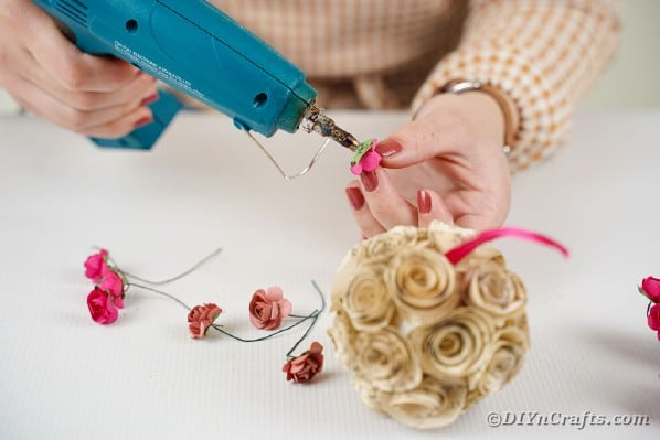 Gluing miniature roses to paper rose ball