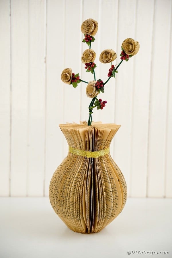 Old book page vase in front of white shiplap wall
