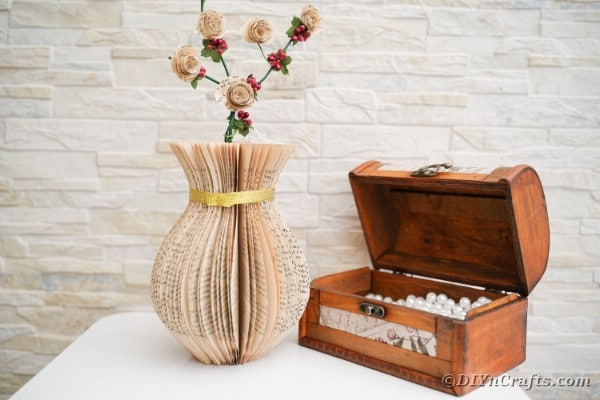Paper vase on table by open chest