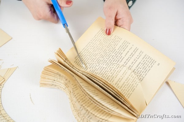 Using scissors to cut out book page