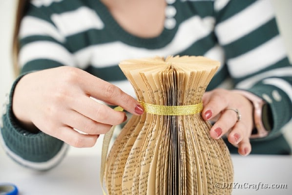 Gluing ribbon around vase
