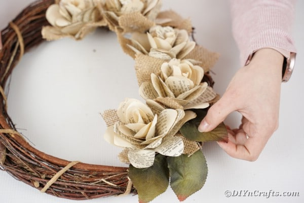 Woman gluing leaves on wreath