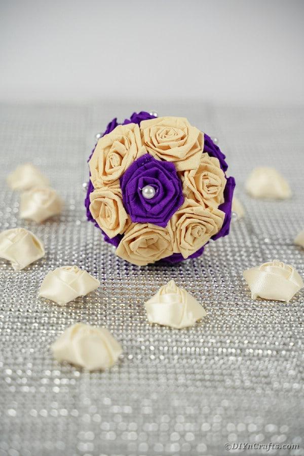 Purple and cream rose ball on burlap