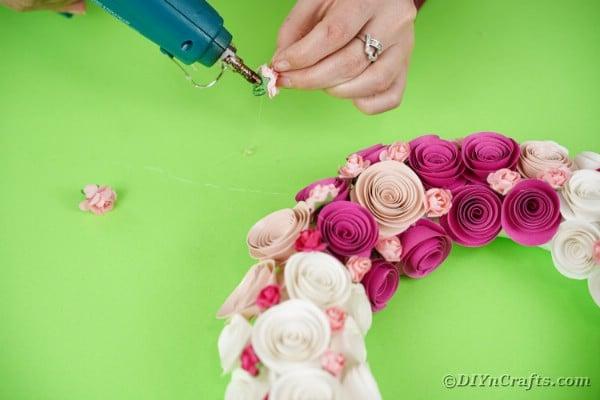 Gluing roses onto unicorn wreath