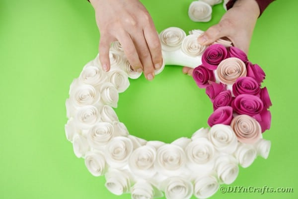 Gluing paper flowers to wreath form