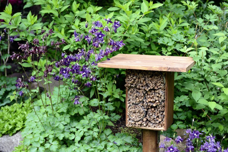 Simple bee hotel on a stand placed in the garden.