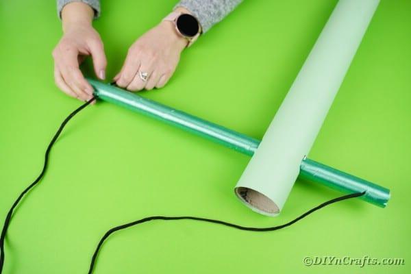 Threading twine through cardboard tube