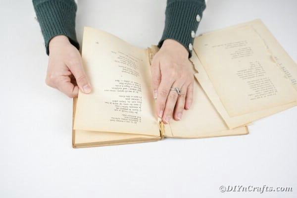 Woman tearing pages from an old book