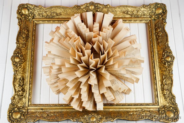 Book page fan flower in gold frame on white boards