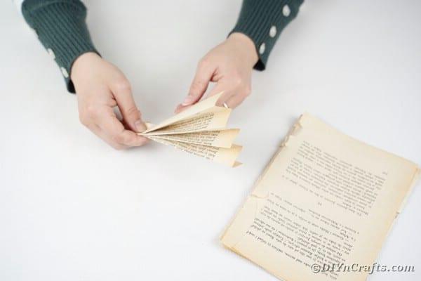Woman folding book page into fan shape