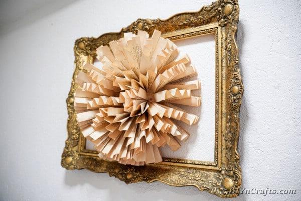 Paper fan flower in frame on white wall