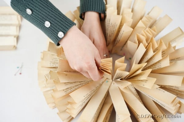 Woman attaching paper fans to wreath form