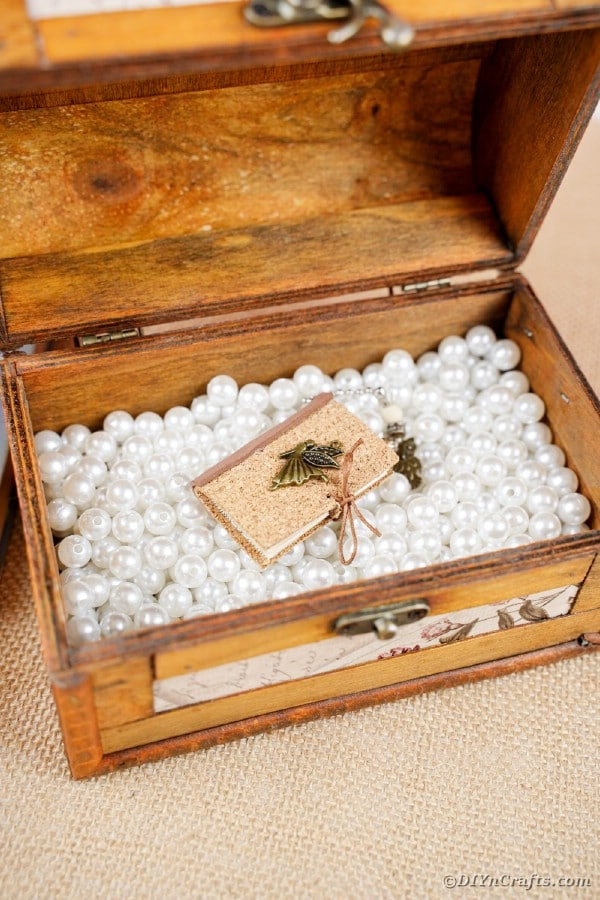 Miniature book inside a wooden chest with beads