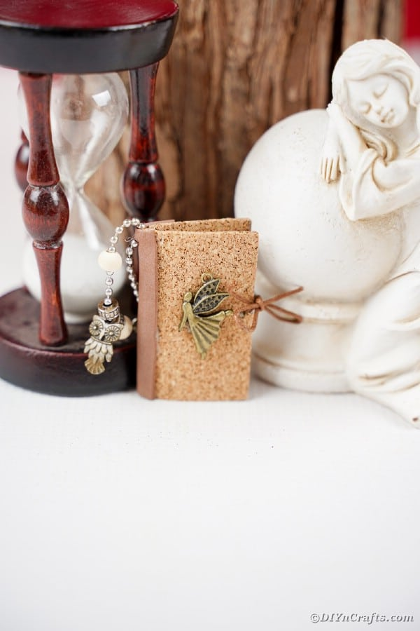 Mini book keychain laening against an hourglass