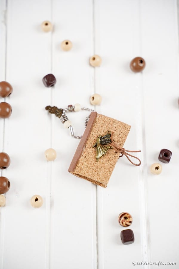 Miniature book keychain on white table with wooden beads