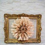 Framed paper fan flower on brick wall