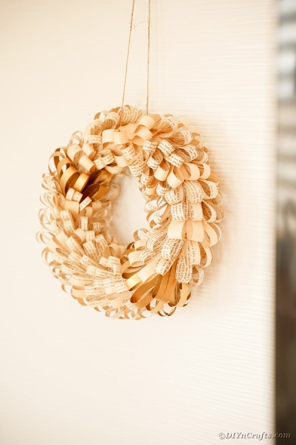Old book page wreath on cream wall