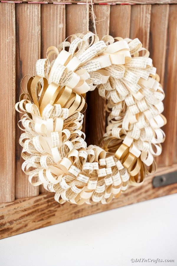 Book page wreath hanging against wooden slats