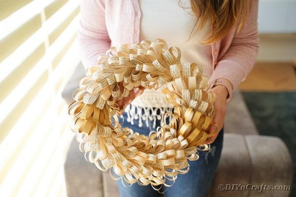 Woman holding fringed wreath
