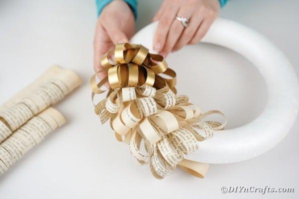 Gluing fringe paper on styrofoam wreath form
