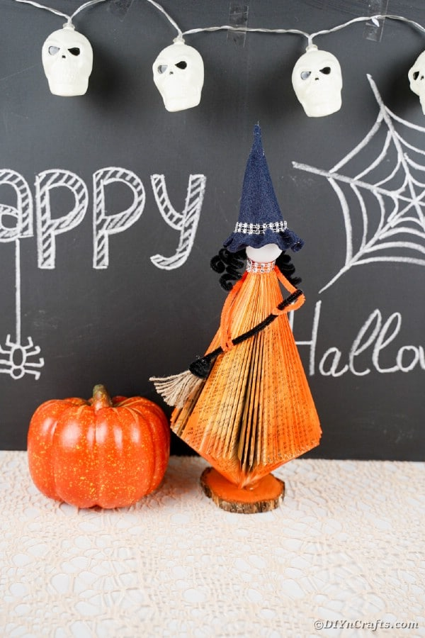 Old book witch in front of chalkboard