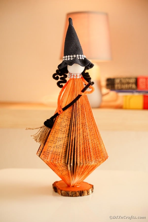 Paper witch on side table by bookcase