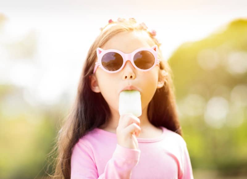 Young girl eating popsicles