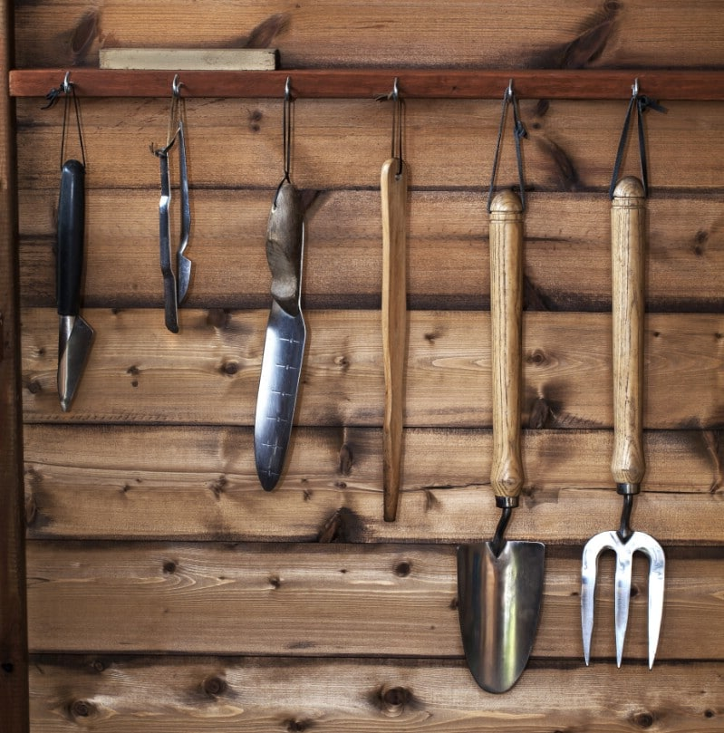 Cleaned and polished gardening tools hung on the wall.