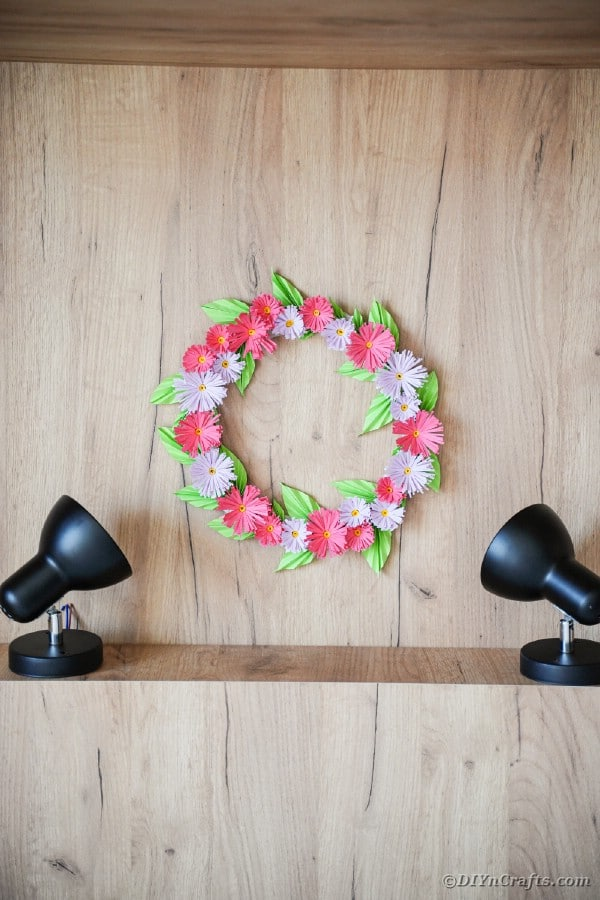 Flower wreath on wood wall with lights