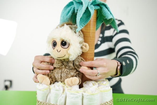 Adding monkey to diaper cake