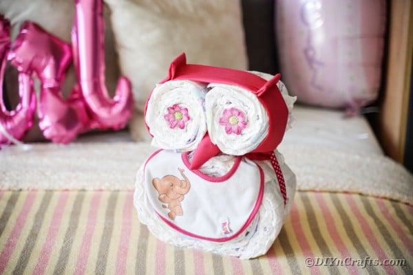 Owl diaper cake laying on striped bedding