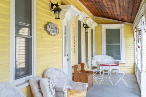 Yellow porch with white wicker