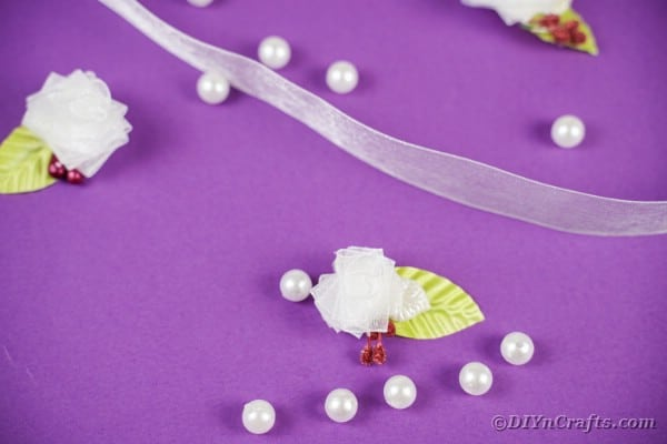 Miniature ribbon flowers on purple surface