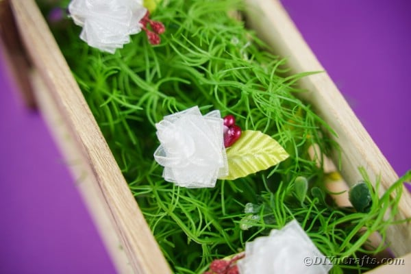 Ribbon flowers in box with fake grass