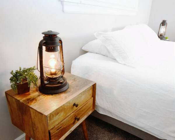 Electric lantern by white bed