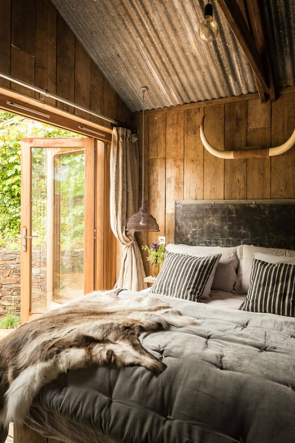 Wood wall with antlers above bed