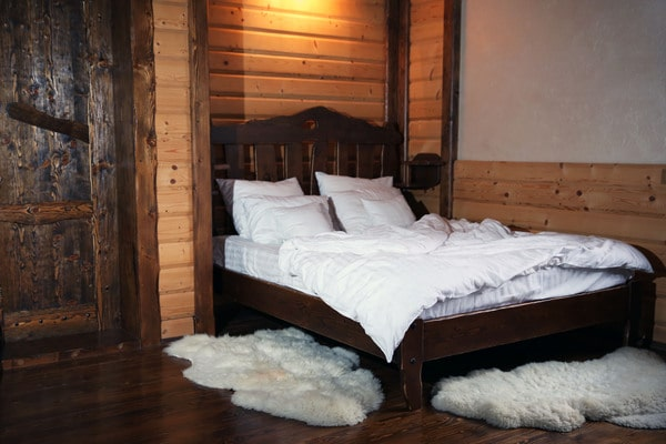 Dark wood bed frame and white rugs