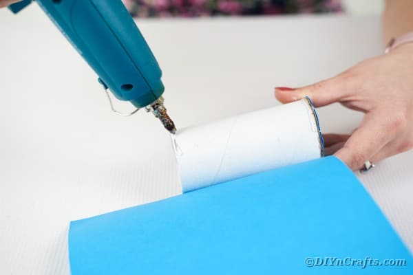 Gluing paper to toilet paper roll