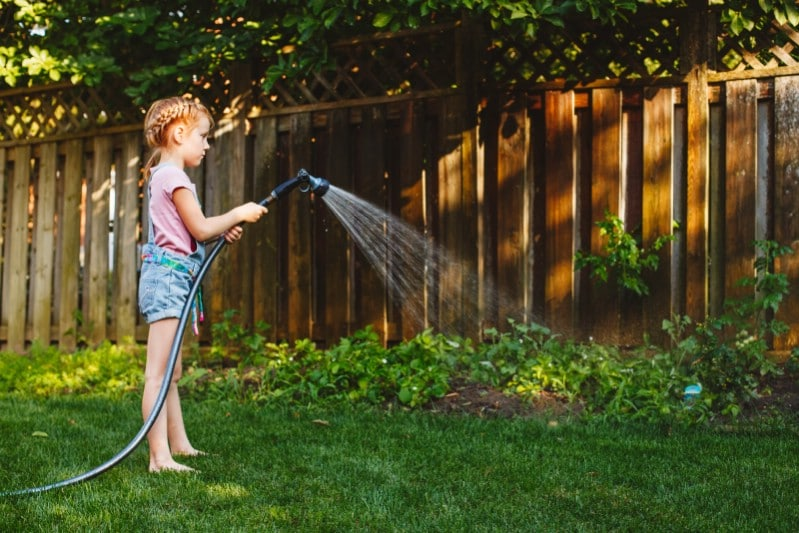 Little girl watering the garden.