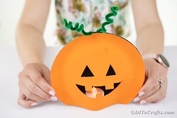 Placing pumpkin plates over candle