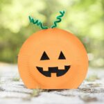 Paper plate pumpkin on rock