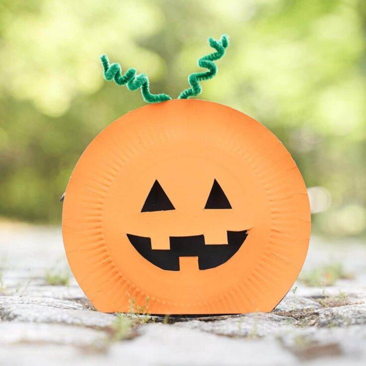 Paper plate pumpkin on rock