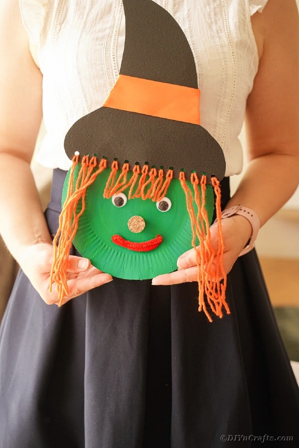 Woman holding paper plate witch face