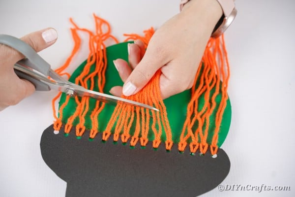 Trimming bangs on paper plate witch