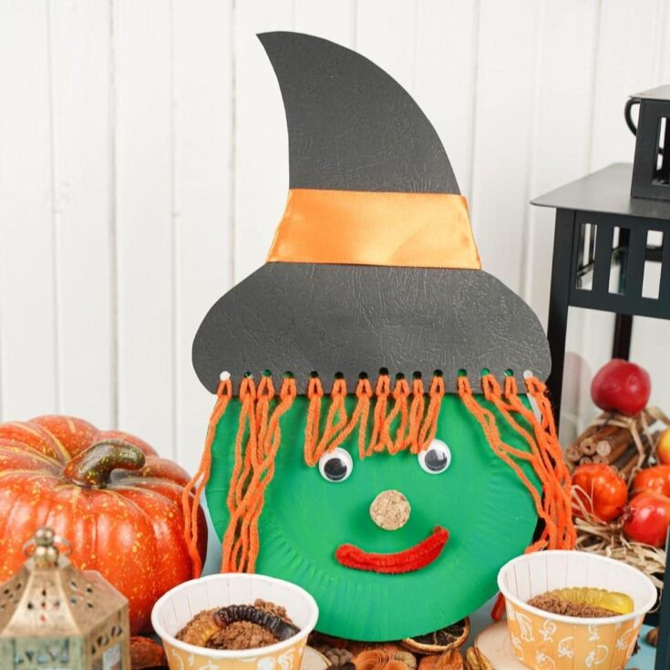 Paper plate witch face with Halloween decorations