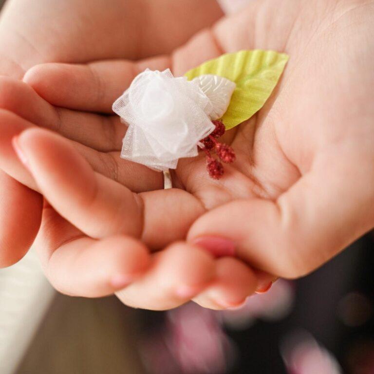 Woman holding miniature ribbon flower