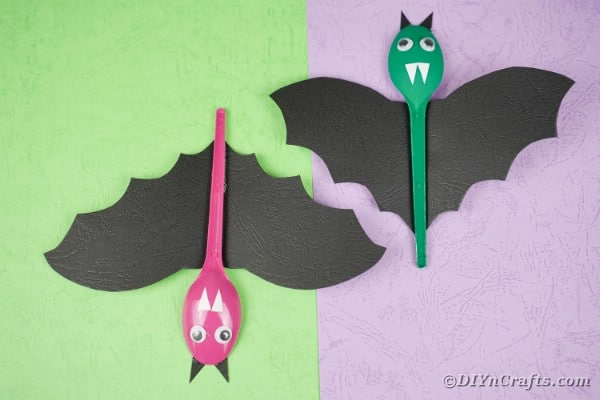 Hanging spoon bats on green and purple background