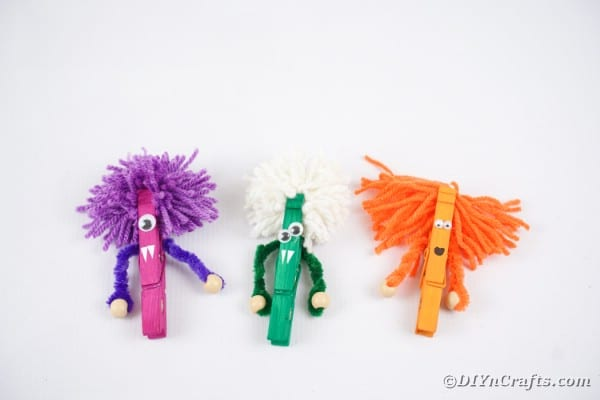 Clothespin monsters on white surface